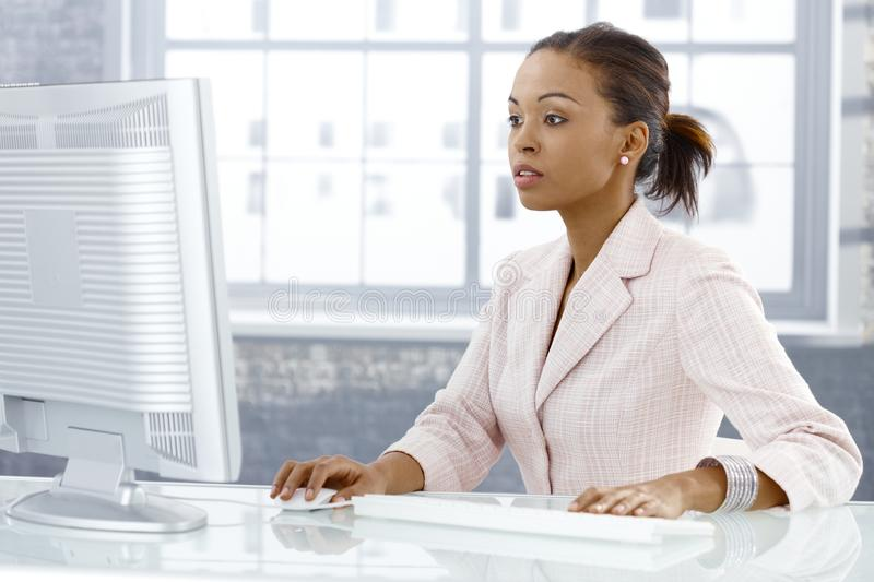 Businesswoman concentrating on work. Businesswoman concentrating on computer work, looking at monitor, sitting at desk royalty free stock image