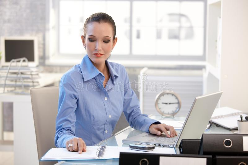Businesswoman concentrating on work royalty free stock image