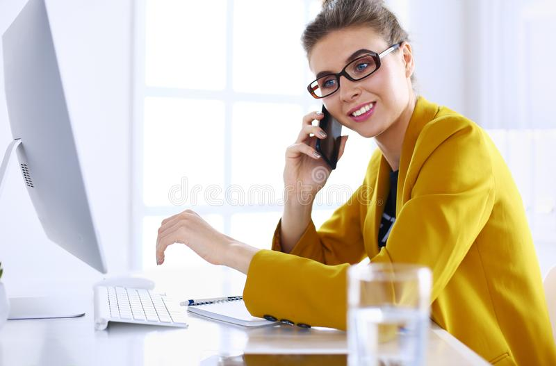 Businesswoman concentrating on work, using computer and cellphone in office stock photo