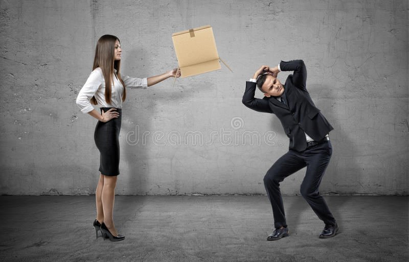 Businesswoman on concrete background holding a carton box to a cowering man. Corporate world. Career path. Job requirements royalty free stock image
