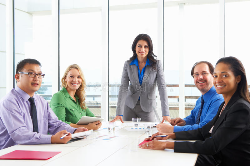 Businesswoman Conducting Meeting In Boardroom. Businesswoman Conducting Team Meeting In Boardroom royalty free stock image