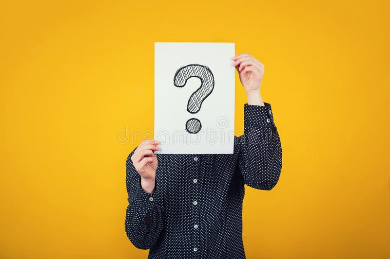 Businesswoman covering face using a white paper sheet with drawn question mark, like a mask, for hiding her identity.  on stock photo