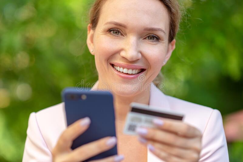 Businesswoman with a credit card and phone makes purchasing outdoors. Successful  woman is using smart phone and bank card for stock image