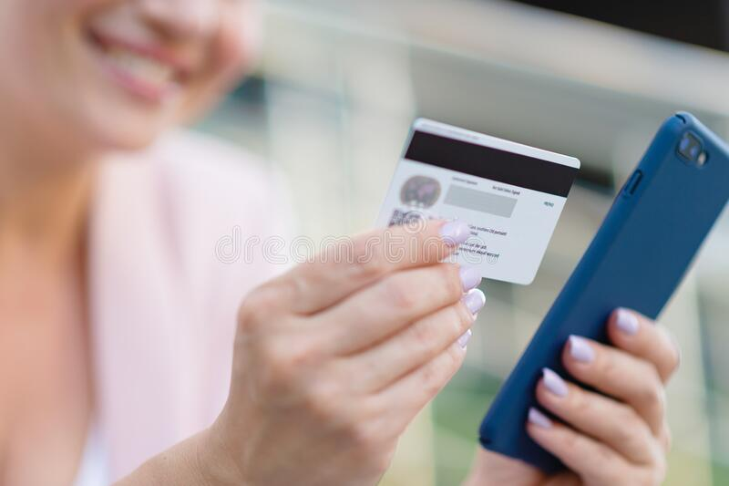 Businesswoman with a credit card and phone makes purchasing outdoors. Successful  woman is using smart phone and bank card for royalty free stock images