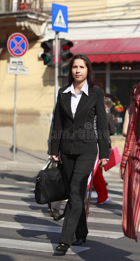Businesswoman crossing the street stock photo