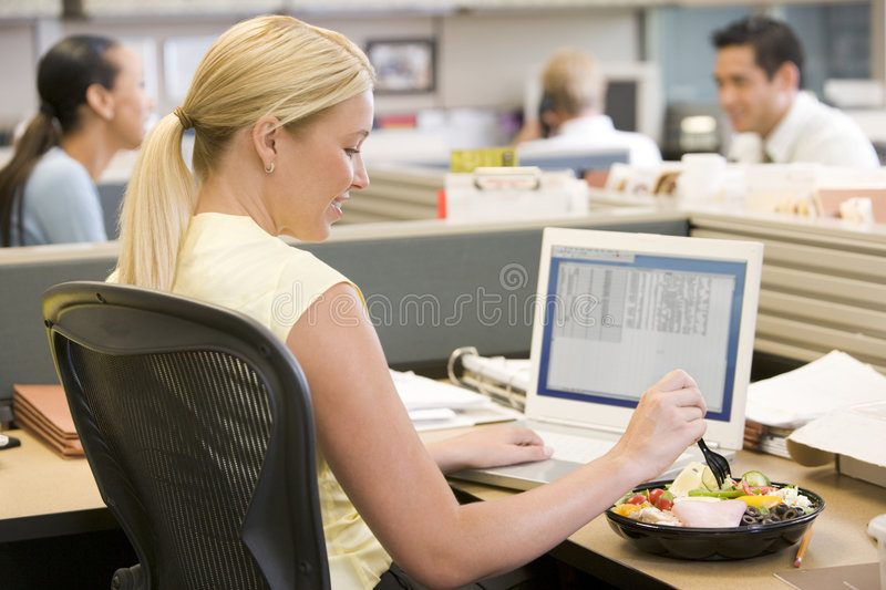 Businesswoman in cubicle using laptop and eating s stock photos