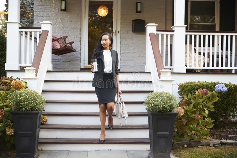 Businesswoman With Cup Of Coffee Leaving Suburban House For Work royalty free stock photo