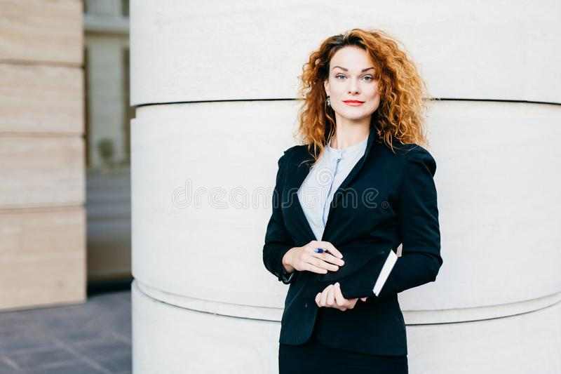 Businesswoman with curly light hair, red painted lips, wearing white blouse, black jacket and skirt, holding notebook with pen, go. Ing to write necessary notes royalty free stock photo