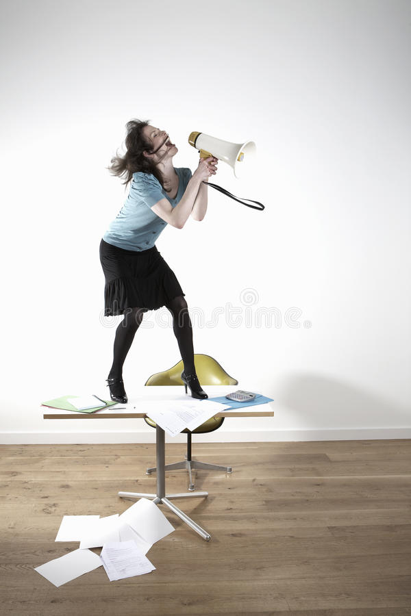 Businesswoman On Desk Screaming Into Megaphone stock photography