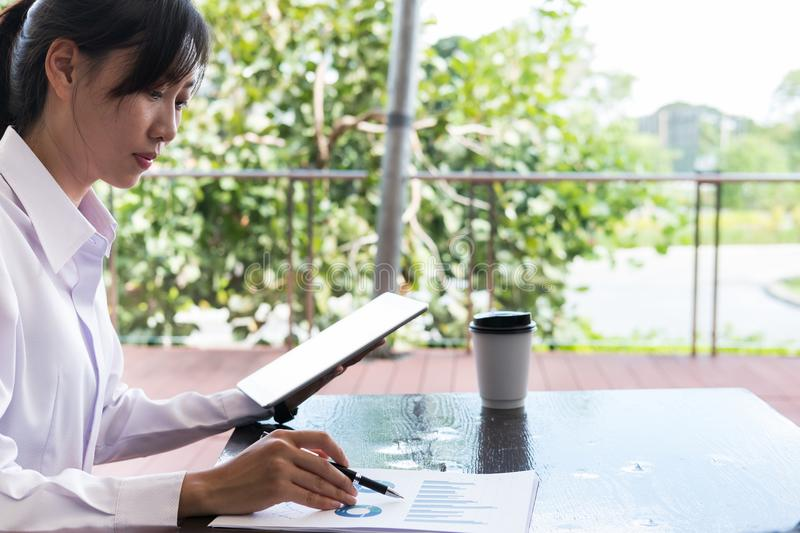 Businesswoman with digital tablet & financial summary graph sitting outside office building. young asian woman analyzing. Beautiful businesswoman with digital royalty free stock image