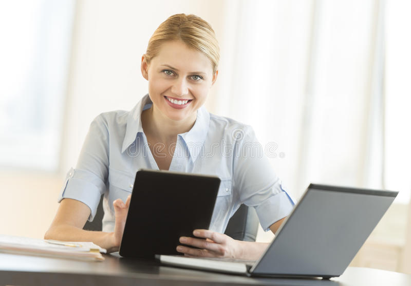 Download Businesswoman With Digital Tablet And Laptop Sitting At Desk Stock Photo - Image: 32429842