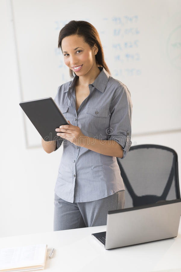 Download Businesswoman With Digital Tablet Standing By Desk In Office Stock Image - Image: 32429697