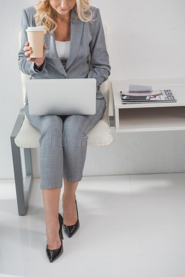 Businesswoman. With disposable cup of coffee working with laptop stock image