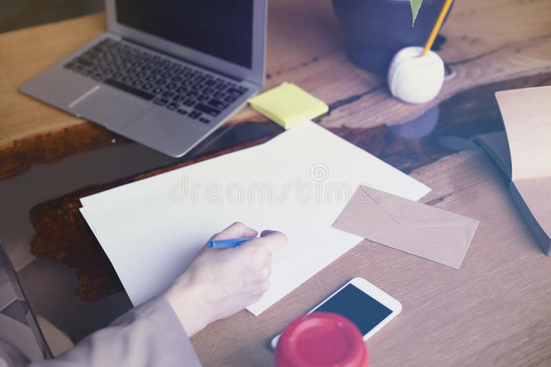 Businesswoman with documents paper sheet in loft modern office, working on laptop computer. Team working, business people. Space for design layout royalty free stock image