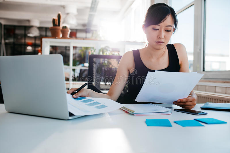 Businesswoman doing paperwork at her workplace. Portrait of young asian woman reading documents at her desk. Businesswoman at her workplace doing paperwork stock images