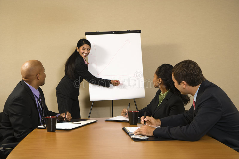 Businesswoman doing presentation. Businesspeople sitting at conference table smiling while businesswoman gives presentation royalty free stock image