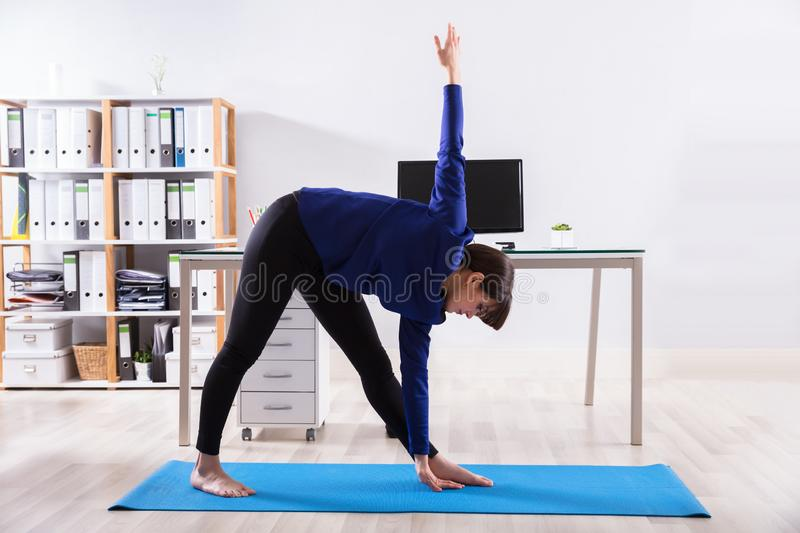 Businesswoman Doing Workout In Office stock photo