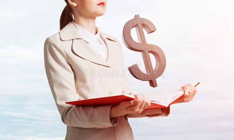 Businesswoman with dollar sign above opened book royalty free stock photography