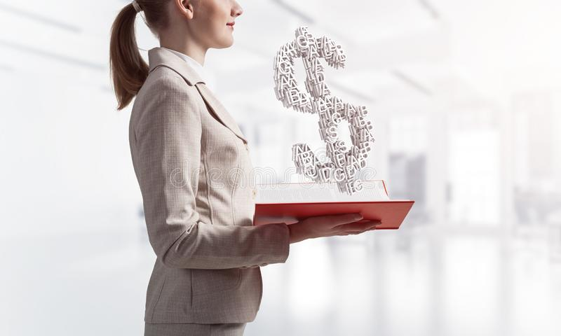 Businesswoman with dollar sign above opened book stock photos