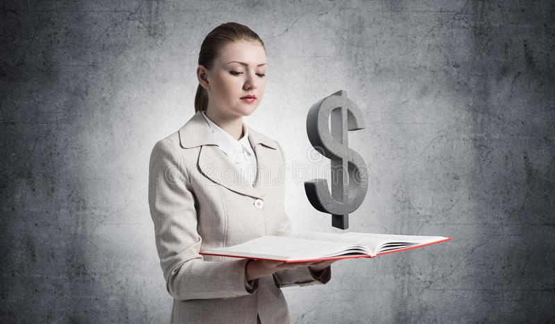 Businesswoman with dollar sign above opened book royalty free stock images