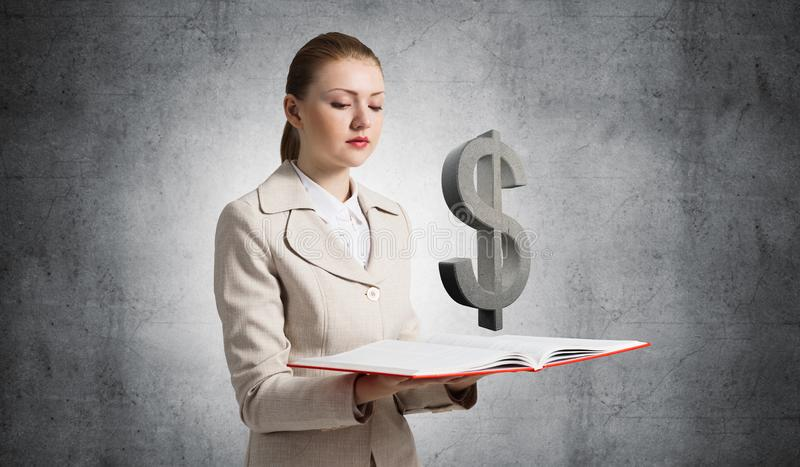 Businesswoman with dollar sign above opened book royalty free stock photo