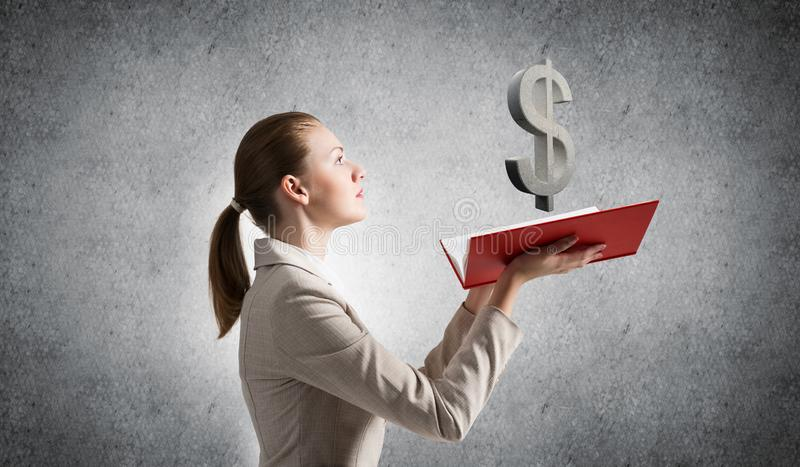 Businesswoman with dollar sign above opened book royalty free stock image