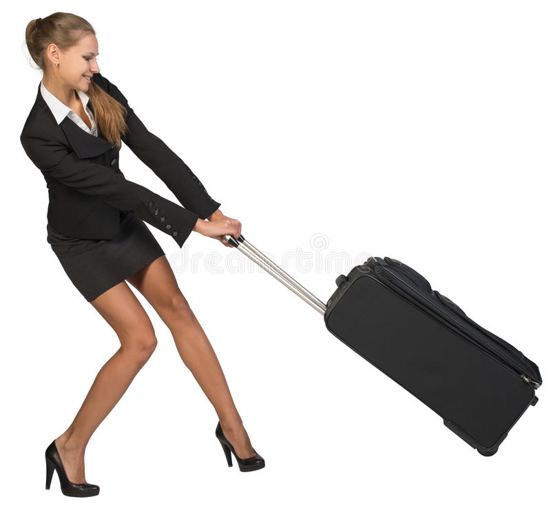 Free Businesswoman Dragging Heavy Wheeled Suitcase At Royalty Free Stock Photo - 49830345