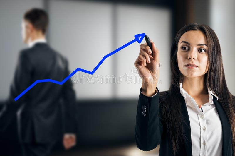 Businesswoman drawing blue arrow stock image