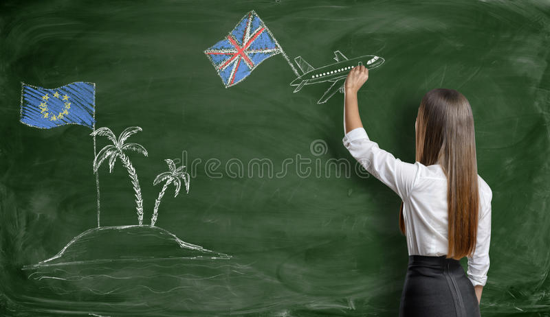 Businesswoman drawing plane with british flag that flies away from an EU island. Businesswoman drawing a plane with british flag that flies away from an island royalty free stock image