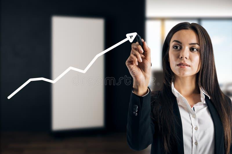 Businesswoman drawing white arrow royalty free stock photo