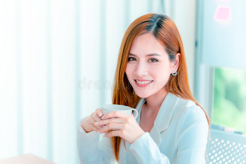 Businesswoman drinking coffee in office windows royalty free stock image