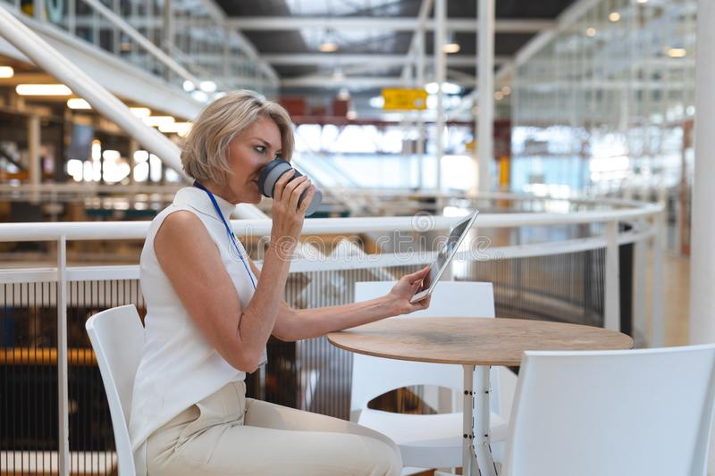 Businesswoman drinking coffee while working on digital tablet at table in a modern office royalty free stock images