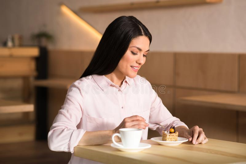 Businesswoman eating cake with coffee. Portrait of attractive businesswoman eating cake with coffee in cafe royalty free stock image