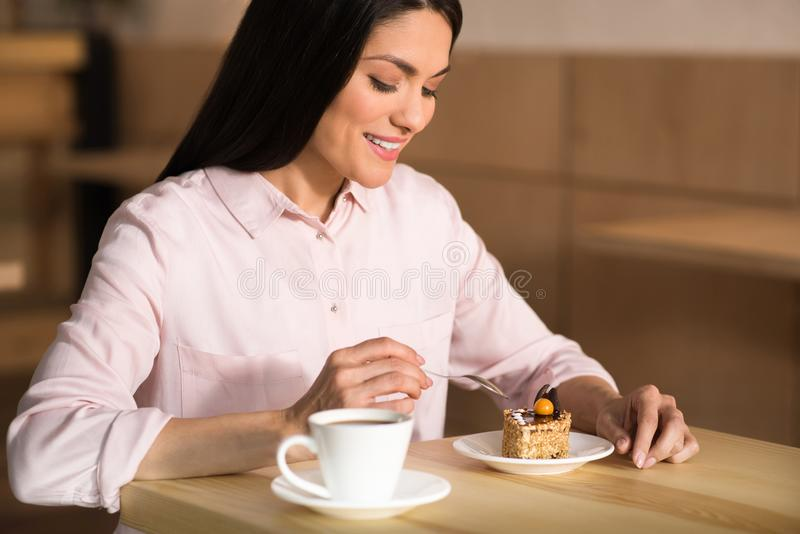 Businesswoman eating cake with coffee. Smiling businesswoman eating cake with coffee in cafe stock images