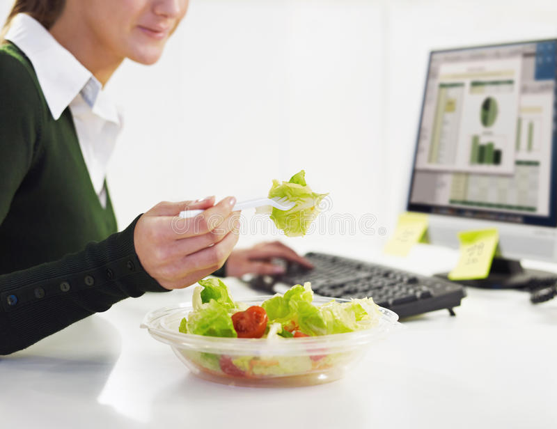 Businesswoman eating salad stock photos