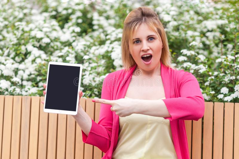 Businesswoman in elegance style sitting in bench on park, holding tablet empty screen and pointing finger to device with opened. Portrait of suprised beautiful royalty free stock images