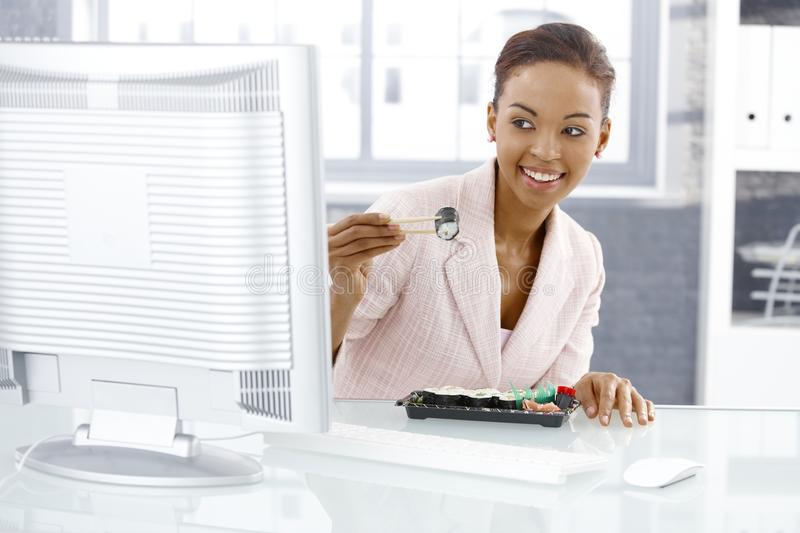 Businesswoman enjoying sushi. Eating with chopstick at desk in lunch break, looking at computer screen, smiling stock photography