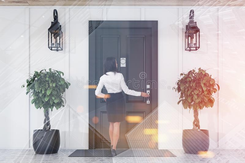 Businesswoman entering black door of white house royalty free stock images