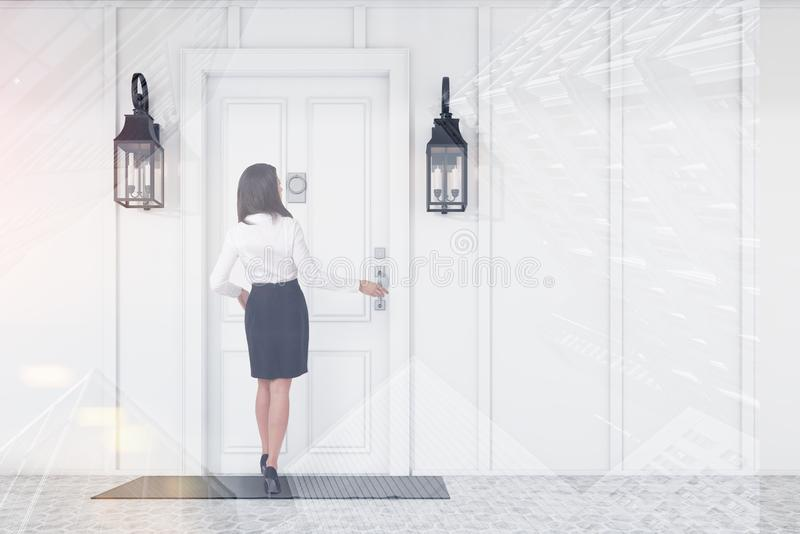 Businesswoman entering white door of white house stock image