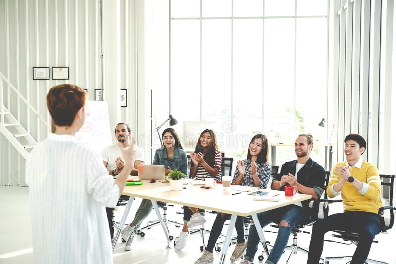 Businesswoman explain ideas to group of creative diverse team at modern office. Rear view of manager gesturing hand standing again stock image