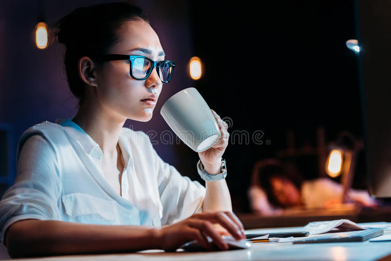 Businesswoman in eyeglasses holding cup while working late in office royalty free stock image