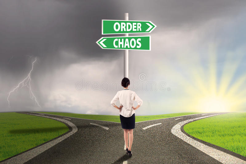 Businesswoman facing a business decision. Businesswoman standing on the road with signpost of order and chaos stock photo