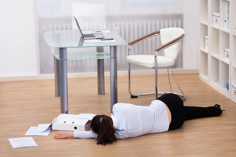 Businesswoman fainted on floor. Exhausted Businesswoman Fainted On Floor At Workplace stock photo