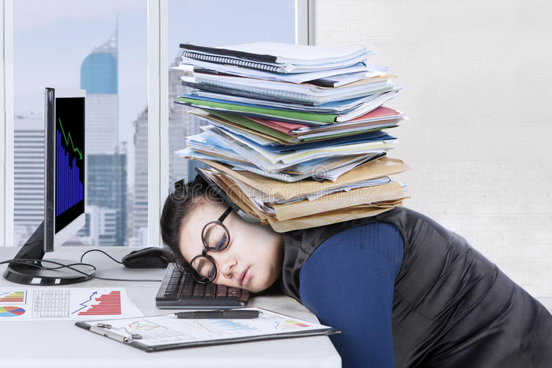 Businesswoman feeling tired with documents stock photo