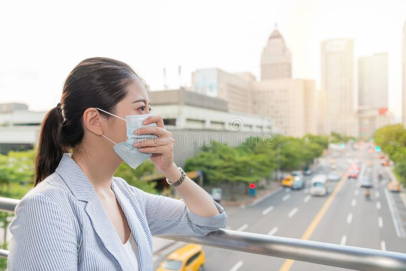 Businesswoman feels allergy from bad air. Beautiful businesswoman feels allergy from bad air quality pollution and wear a mask standing outside royalty free stock photos