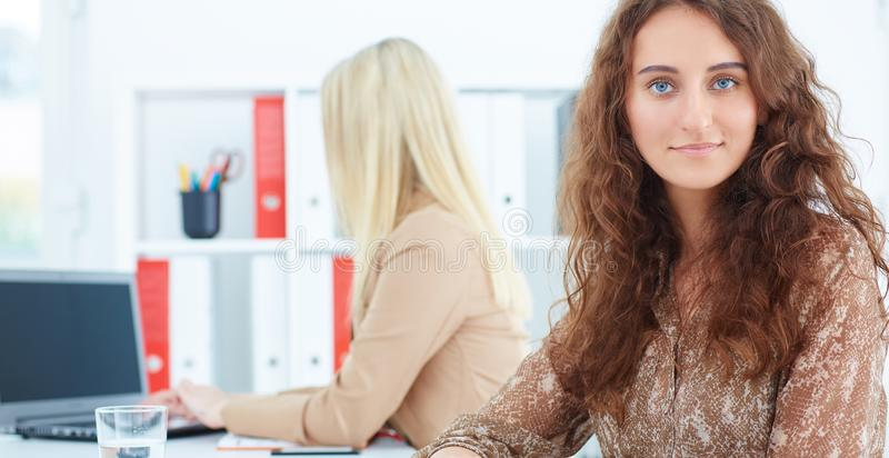 Young businesswoman, with female colleague on the background. Serious business and partnership, job offer concept. stock photo