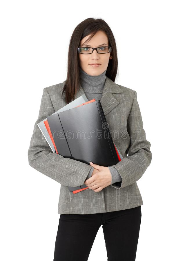 Businesswoman with file folders. Portrait of smart businesswoman in glasses posing with file folders, isolated on white royalty free stock photos