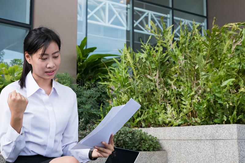 businesswoman with financial graph sitting outside office building. young asian woman analyzing investment charts outdoors. stock photography