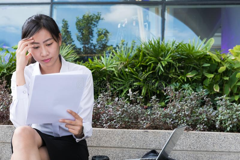 businesswoman with financial graph sitting outside office building. young asian woman analyzing investment charts outdoors. royalty free stock image