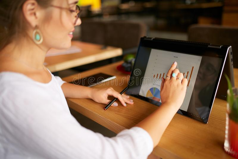 Businesswoman finger touching the chart over convertible laptop screen in tent mode. Freelancer woman using 2 in 1 royalty free stock image